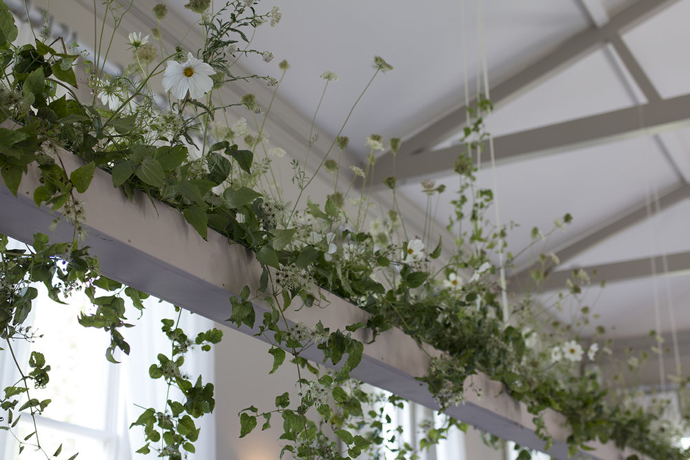 We designed bespoke hanging troughs to suspend 12 metres of greenery above the seated guests in the dining room - these were filled with clematis vines, white cosmos flowers and wild carrot