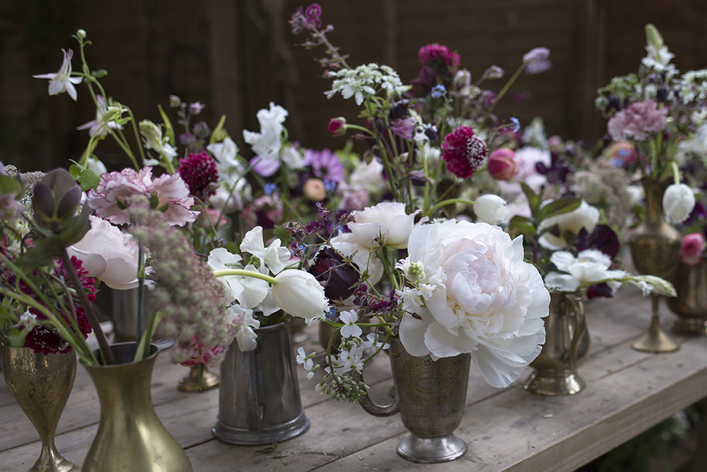 Antique vessels, tankards and vases filled with single specimens in the couple's chosen colour palette