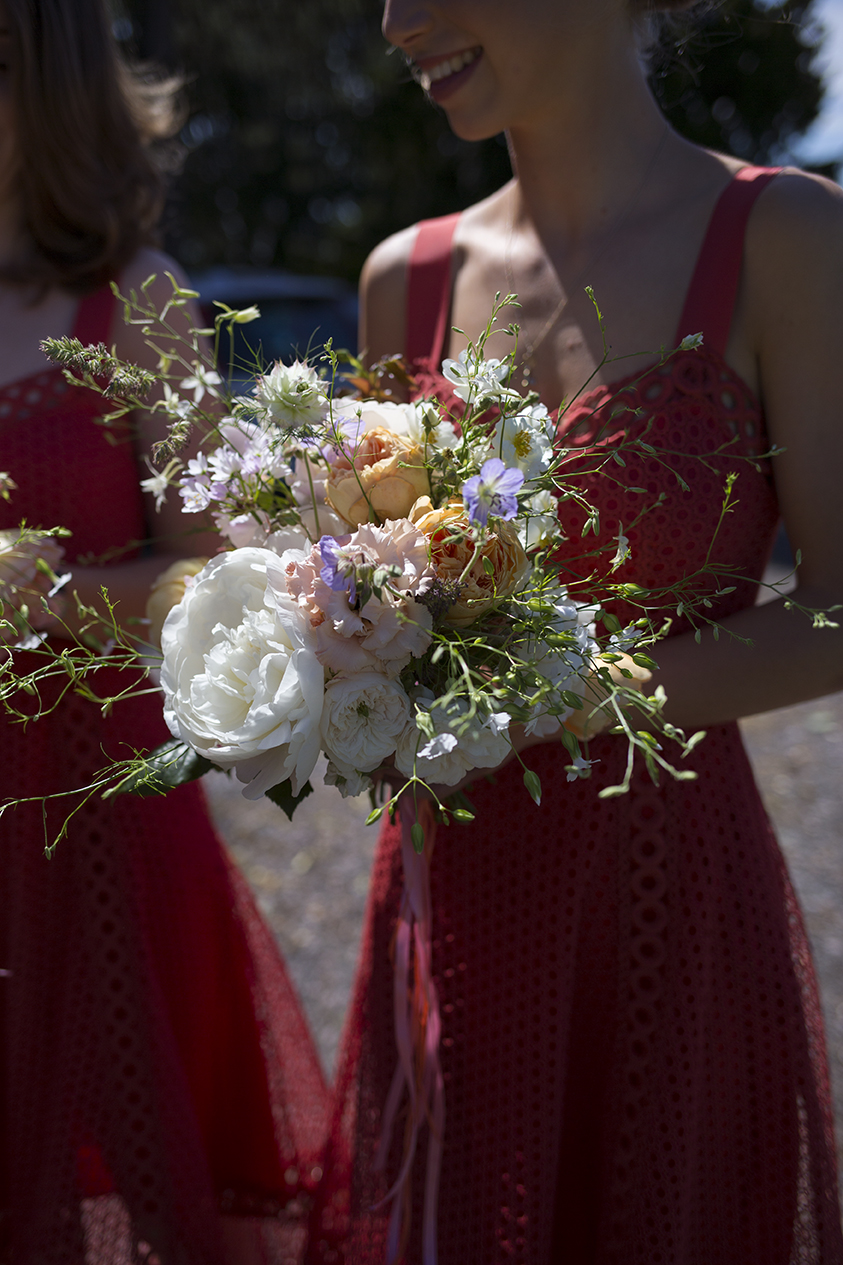 The bridesmaids carried smaller posies of garden roses and larkspur with coral silk streamers