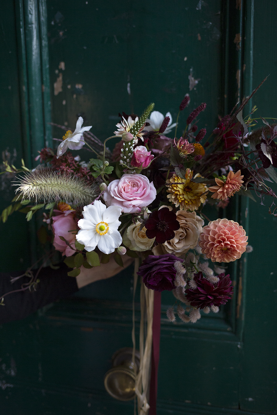 Autumnal bouquet of garden flowers and fluffy grasses, with velvety chocolate cosmos, rusty pom-pom dahlias and crisp white Japanese anemones