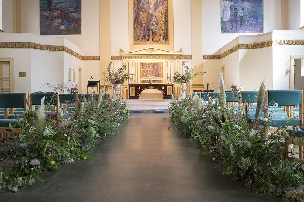 The aisle at St Johns, Waterloo flanked by 24 metres of foliage runners - we used lots of ferns and grasses to create a textural base, then threaded through a few delicate headed flowers and umbels of wild carrot