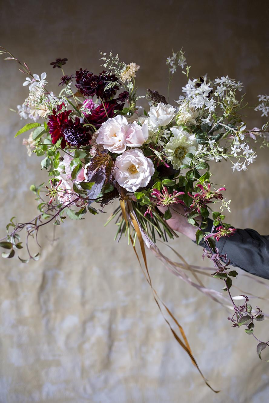 A bridal bouquet of 'English Miss' roses, larkspur, dahlias, diabolo, honeysuckle and bronze clematis vines