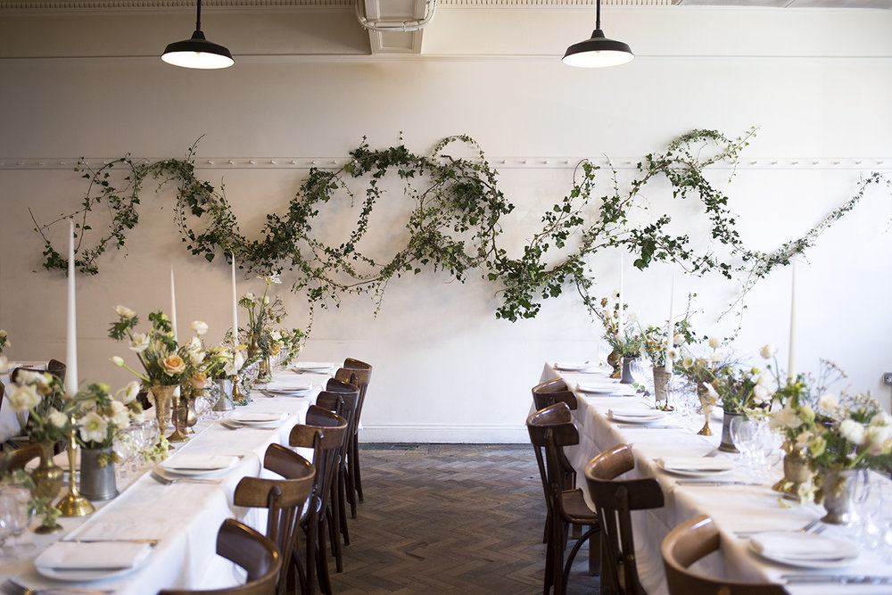 An organic rambling installation of wild ivy dressed the back wall of St John, while the tables were decorated with brass vessels of seasonal flowers - hellebores, anemones, ranunculus and thyme - and lined with pale tapered candles