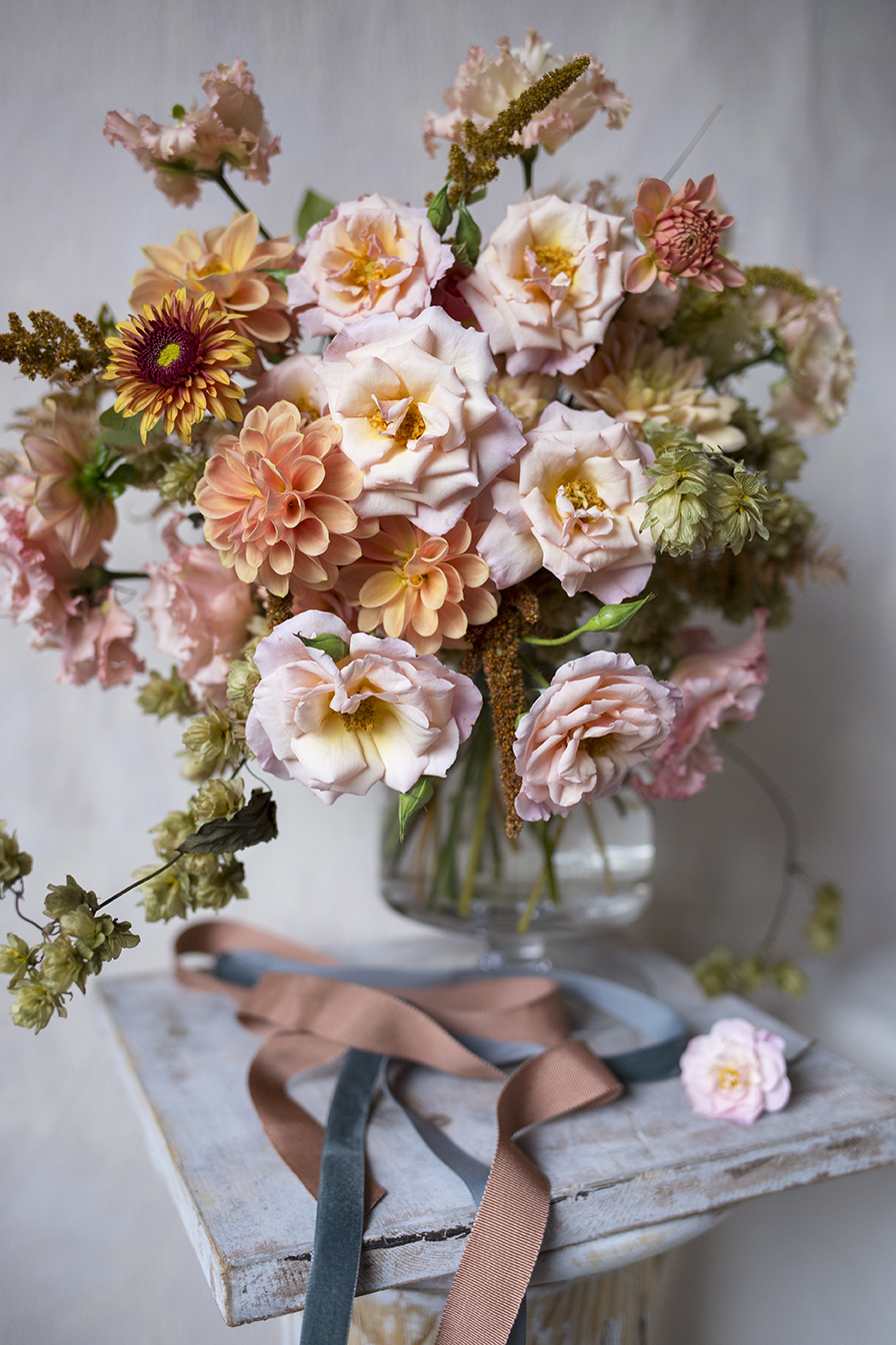 Autumnal bridal bouquet of scented garden roses, dahlias, amaranthus and hops on the vine