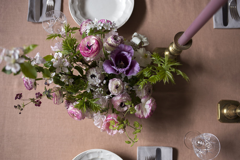 A student's centrepiece featuring pink-ringed picotee ranunculus and plum-coloured geranium flowers.