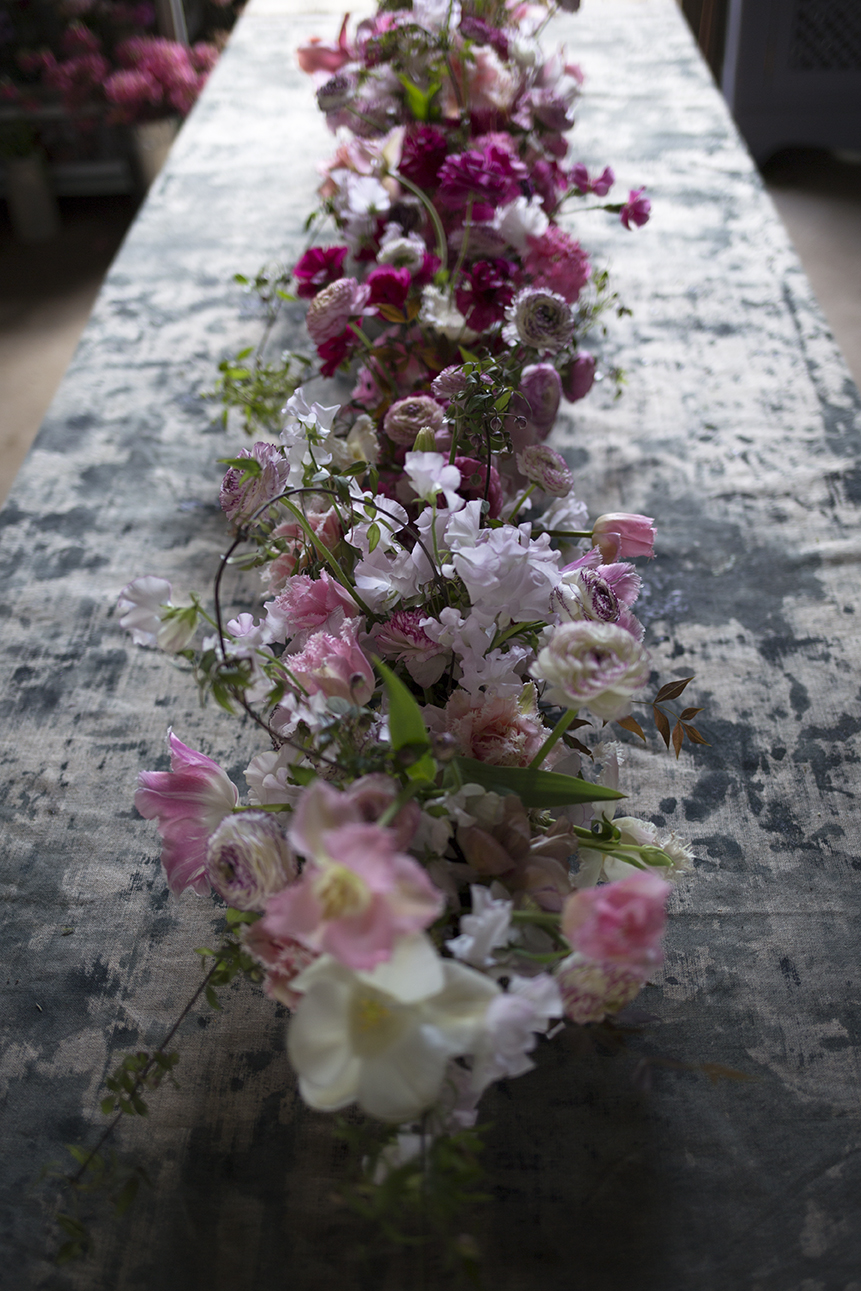 A linear table design created by the group in low concrete troughs - pale pinks with green and bronze spring foliage, accented with pops of deep pink.