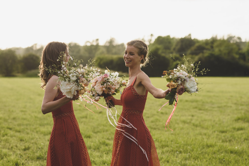 Kate's sisters carried posies of garden roses, larkspur and coral silk streamers. Photographed by  Rik Pennington