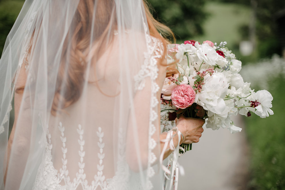 The bride carries her bouquet of ranunculus, sweet peas, saxifraga and colombine down the church walk. Photographed by  Dominique Bader Photography