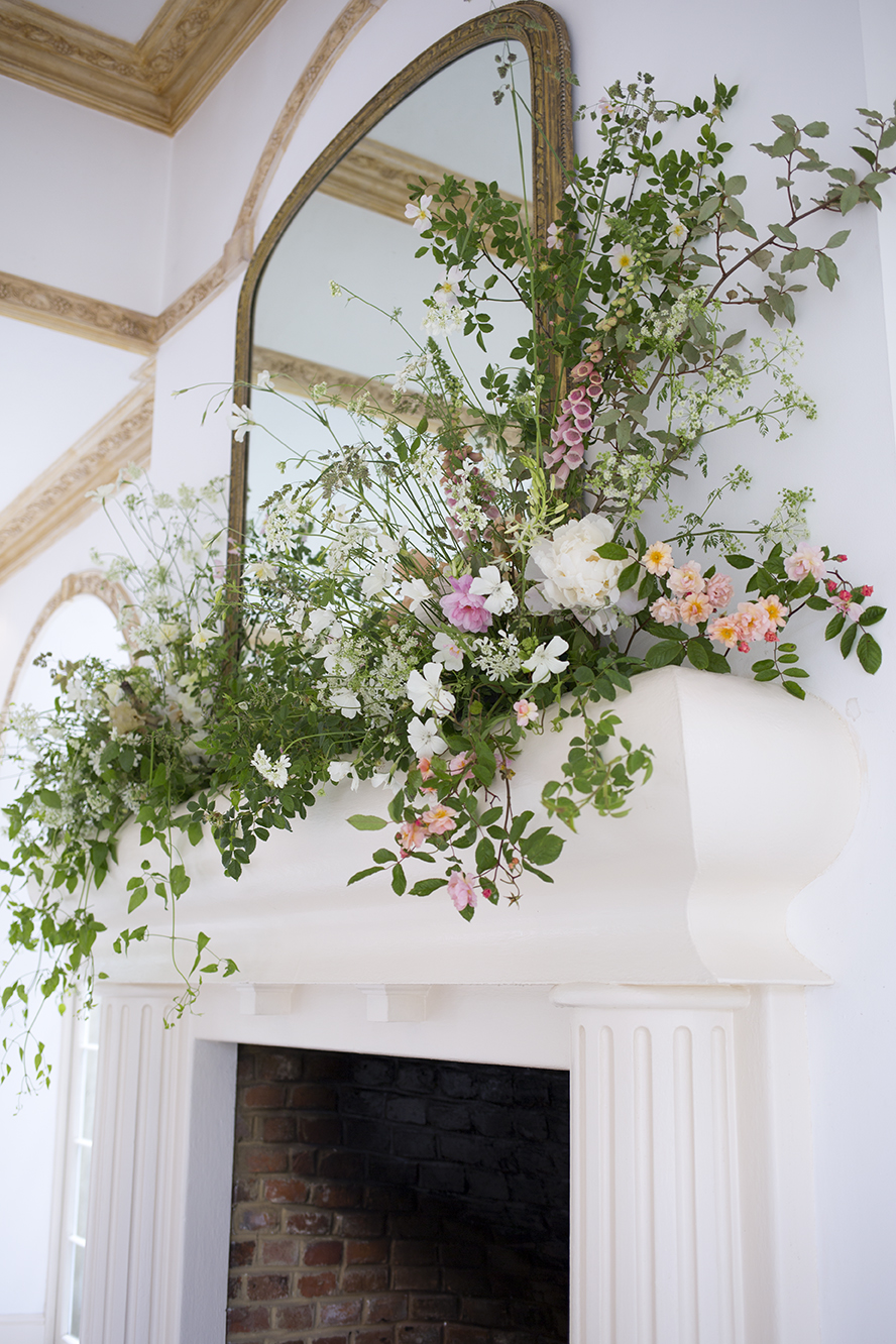 An organic mantel installation for a wedding at  Northbrook Park , Surrey, in late May. Wild dog rose, combined with silverberry, peonies, foxgloves, agrostemma and  Orlaya grandiflora . Tall wisps of cow parsley and intricate grasses added height and airiness to the composition