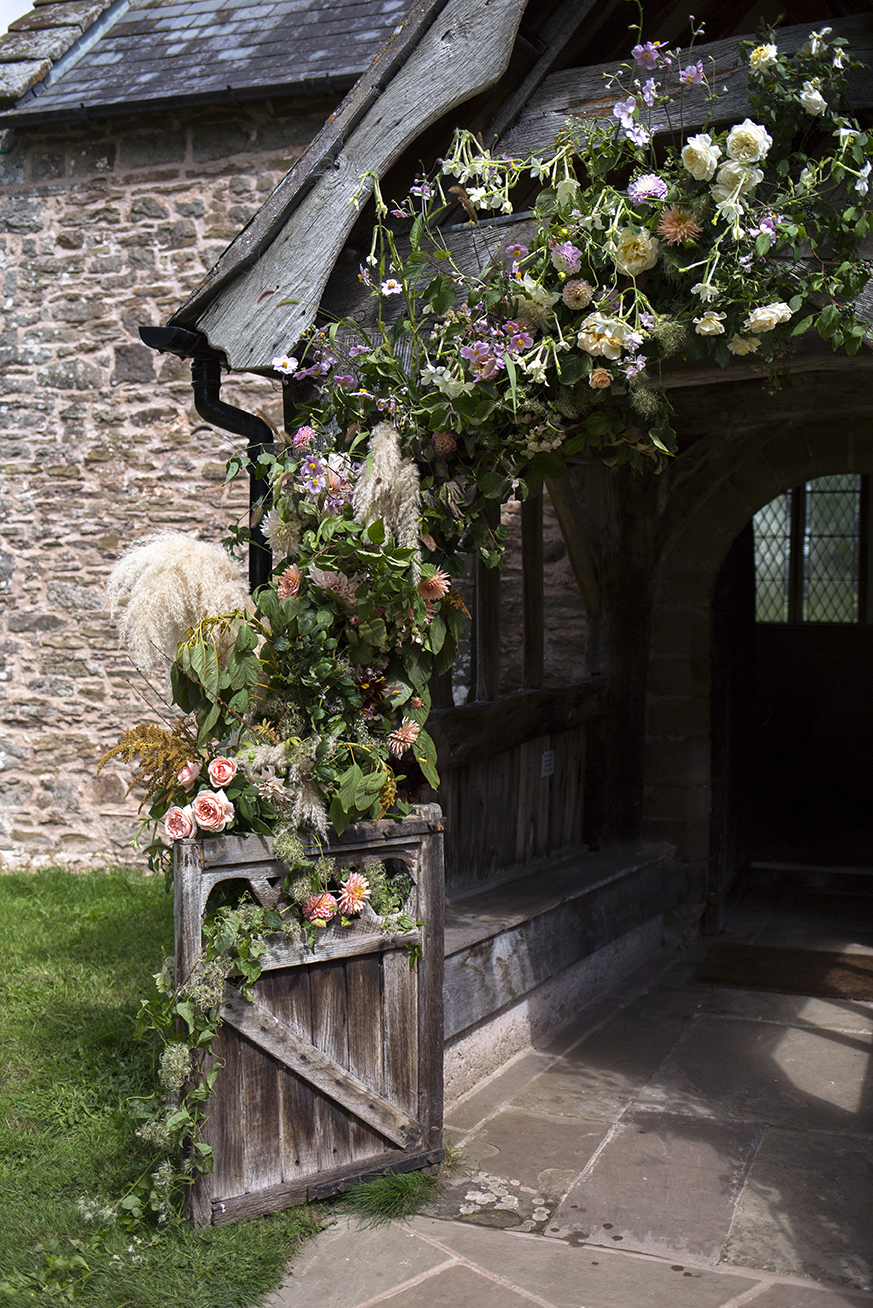 We created an asymmetric arch climbing up the wooden porch sprinkled with garden roses and dahlias, pampas grasses, Japanese anemones, amaranthus and tobacco flowers