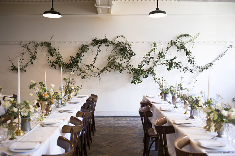An organic rambling installation of wild ivy dressed the back wall of  St John , while the tables were decorated with brass vessels of seasonal flowers - hellebores, anemones, ranunculus and thyme - and lined with pale tapered candles