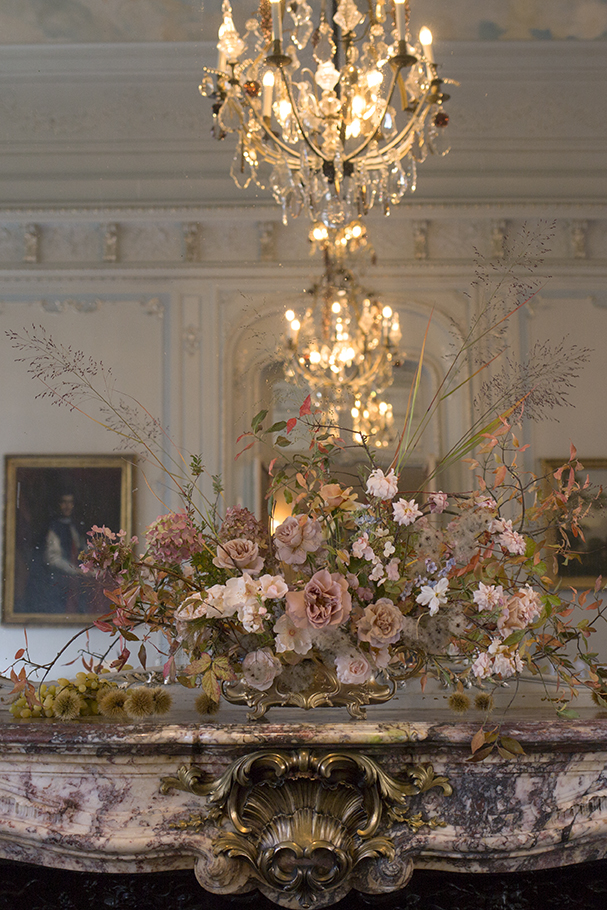 A jardiniere arrangement of brambles, old man's beard and spindle branches, layered with garden roses, hydrangea, tweedia and Japanese anemones and scattered sweet chestnuts along the marble mantelpiece