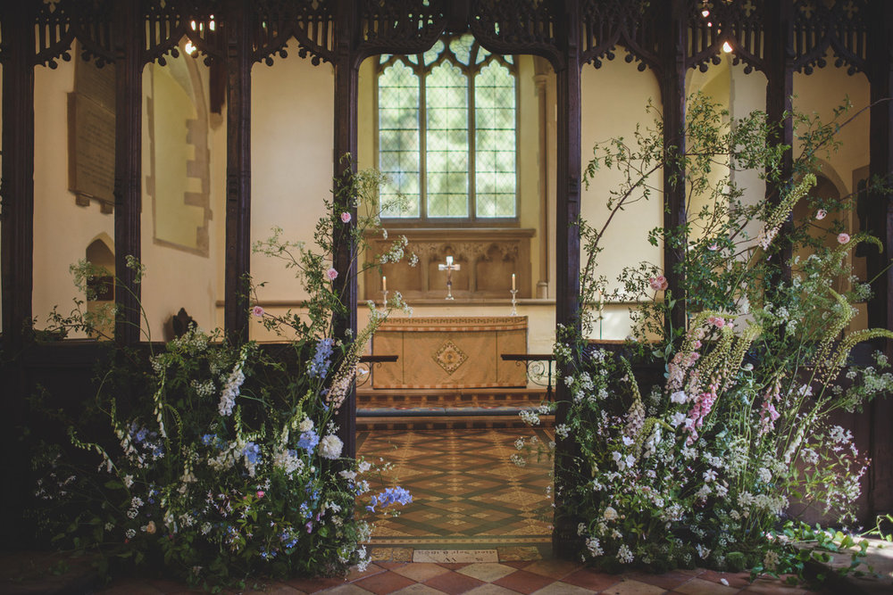 A floral border installation with English seasonal flowers in summery colours, created to appear as if 'growing up from the ground' in a windswept garden, along the base of an intricately detailed wooden rood screen. Photographed by  Rik Pennington