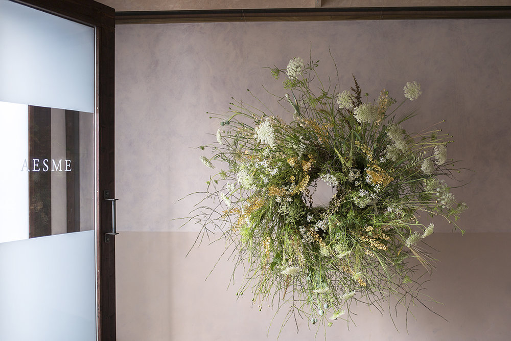 Hanging wreath of dried grasses and seedbeds, with ammi and poppy heads