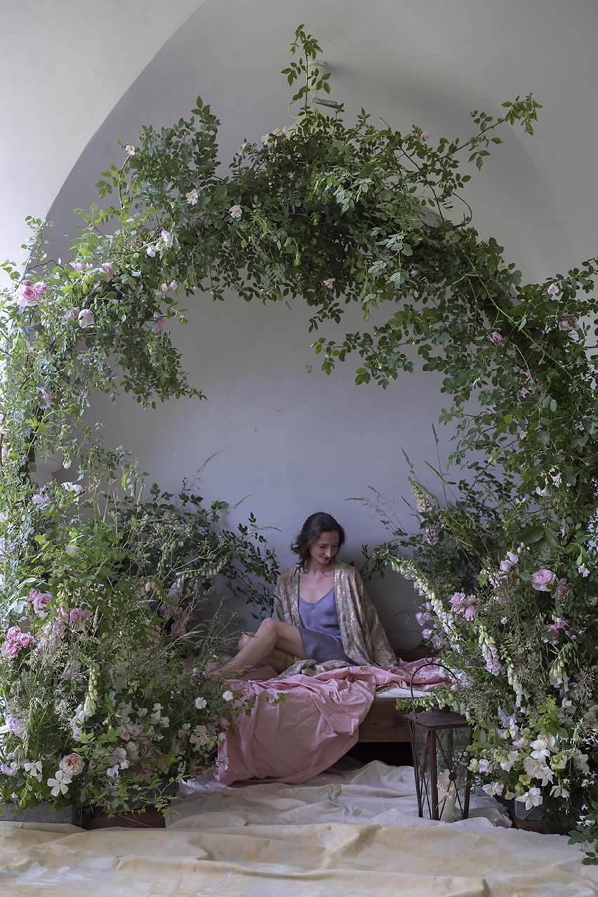An ethereal photoshoot set-up on our Flowers & Photography Retreat 2018. A garden arch and wooden day-bed were dressed with wild dog rose, foraged local foliage, foxgloves and grasses