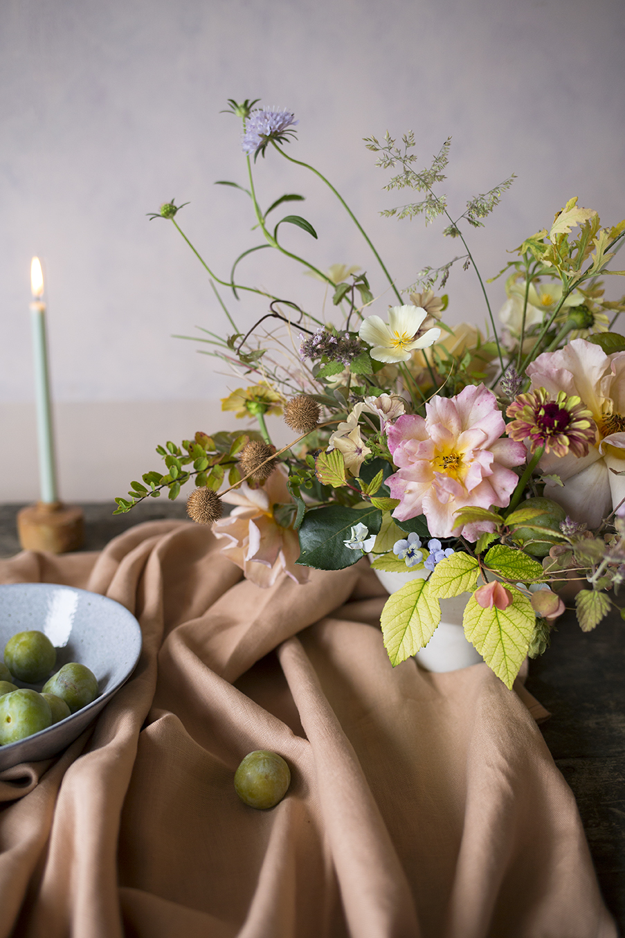 An autumnal flower arrangement with roses and pansies at a workshop at Aesme Flower Studio