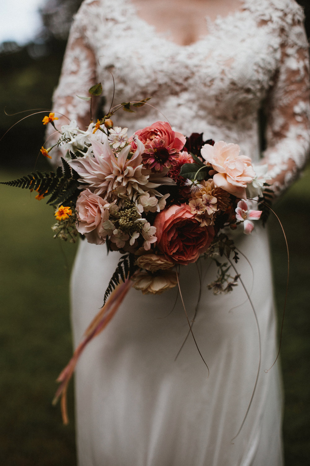 Rhona's ethereal gown called for a glamorous bouquet of 'Jubilee Celebration' roses, 'Cafe au Lait' dahlias, zinnias, godetia, Hydrangea paniculata, phlox 'Creme Brulee' and French marigolds. Photographed by  James Frost