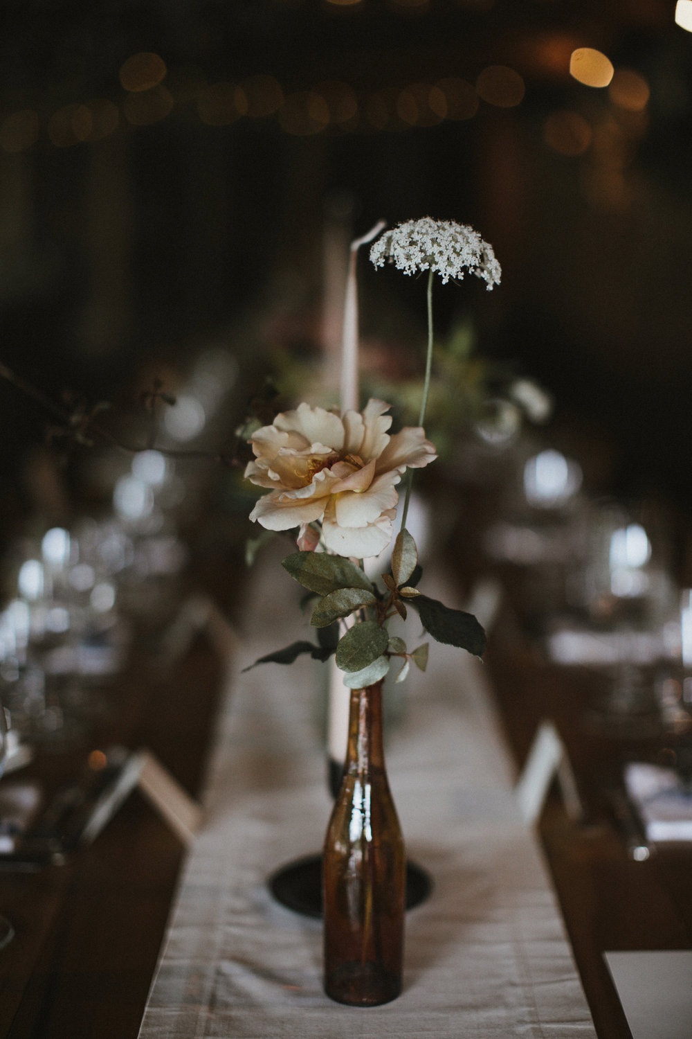 For the tables, flowers in autumnal hues were grouped in gradating colours, and at varying heights, from taupe through pink to rusty oranges, gold and burgundy, in amber and pale blue glass vessels, with the open flames of tall tapered dinner candles flickering above. Photographed by  James Frost