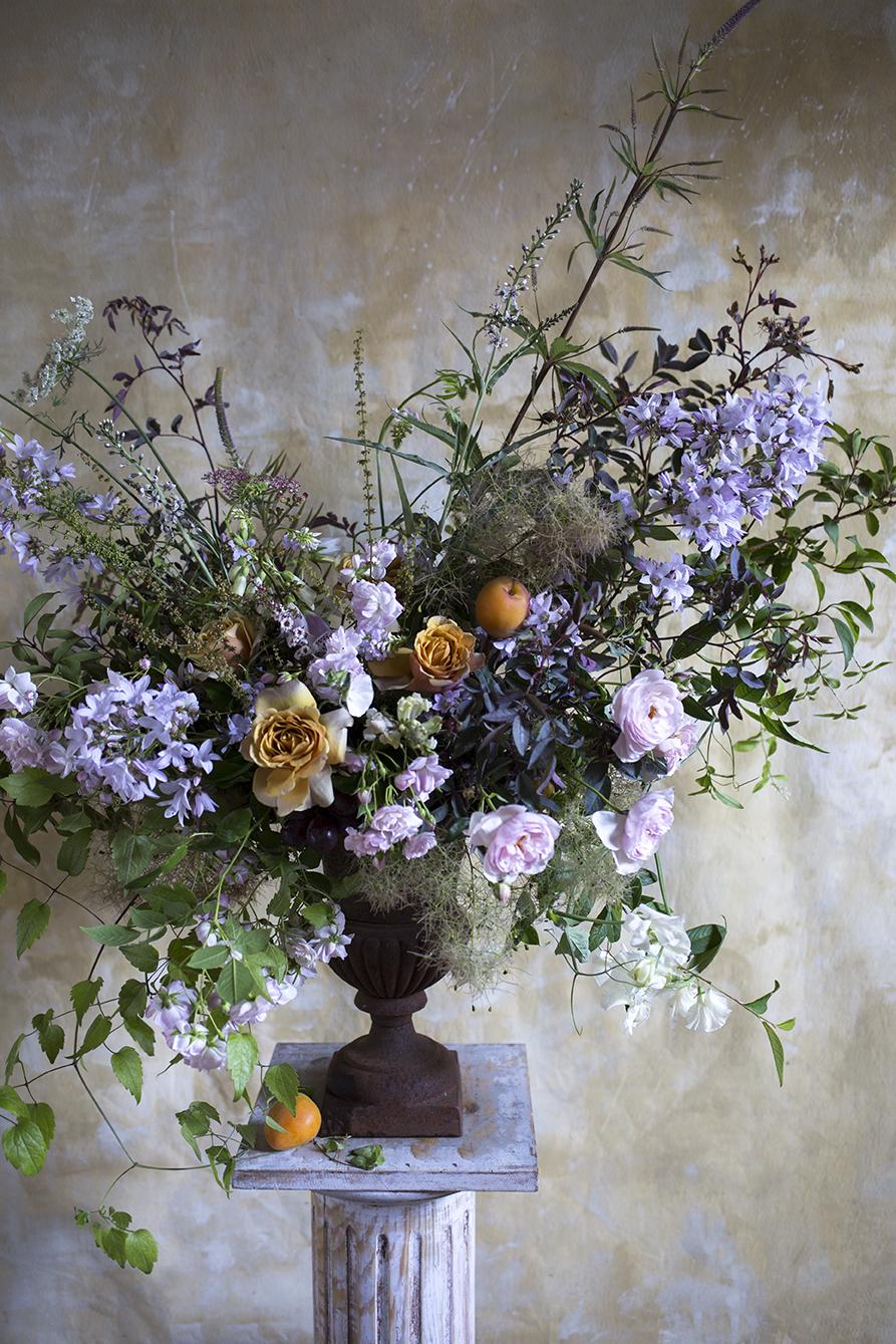 A June urn of roses, campanula, smokebush and apricots