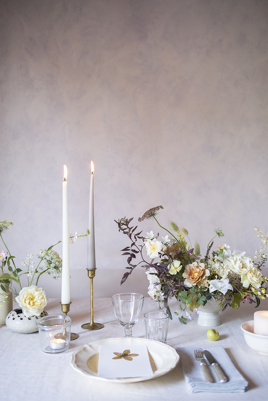 A styled tablescape of footed ceramic bowls spilling with garden flowers