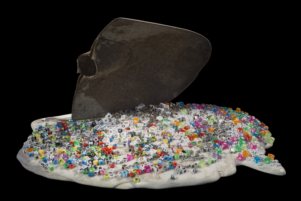 Heed, 2013, iron shovel blade, cast marble, plastic and metal letter beads, 19x9x16 inches