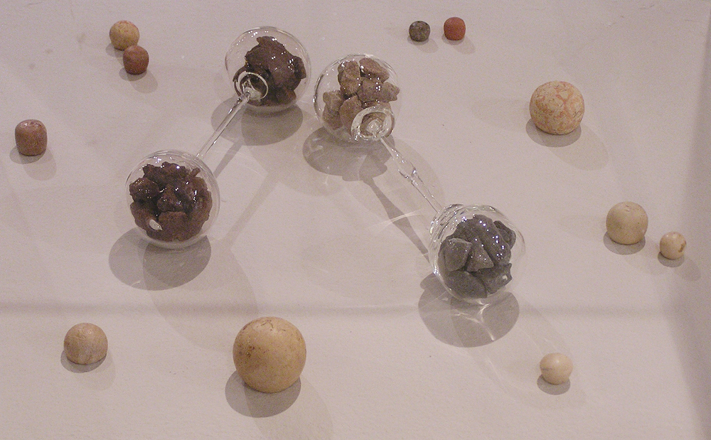 Inheritance , 2004, glass baby barbell rattles filled with stones surrounded by a group of twelve BCE stone shekel weights
