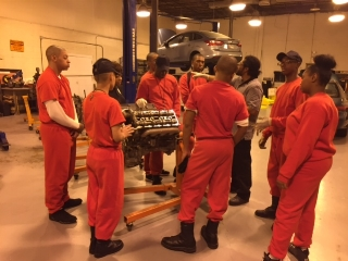 Students receiving instruction in an Excel automotive lab about repairing an engine block