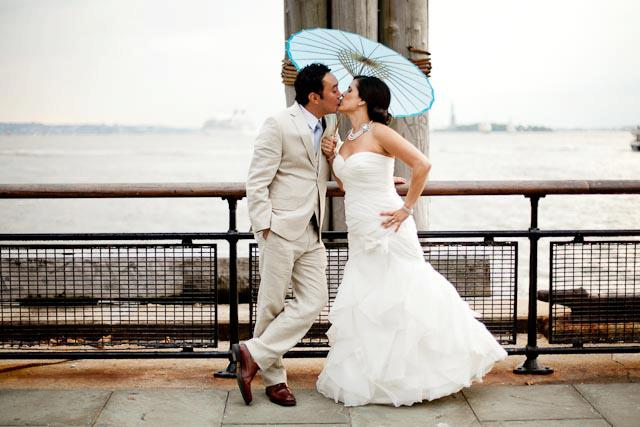 bride-groom-white-suit-parasol-kissing-waterfront