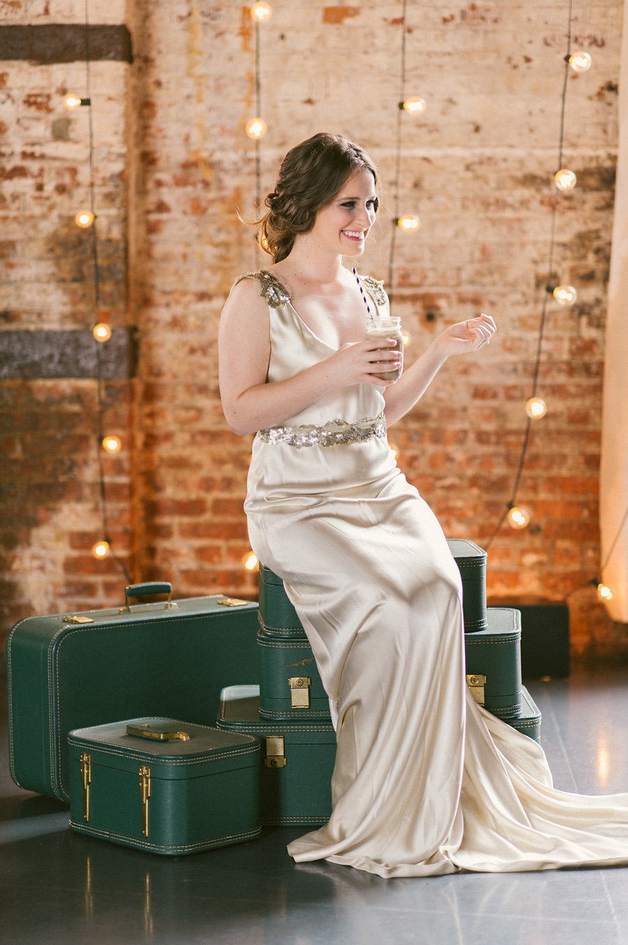 green-vintage-suitcases-string-lights-bride-playful