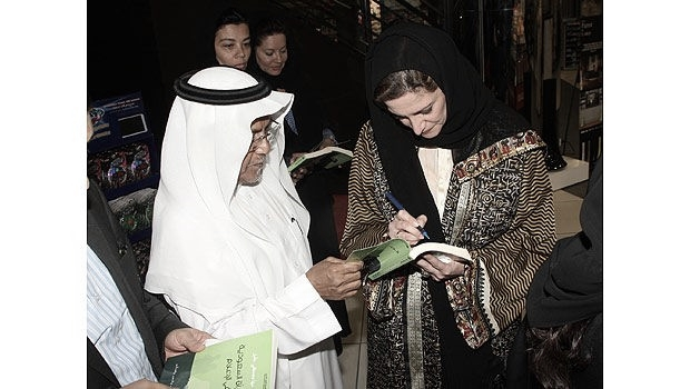 Maha Akeel signing a copy of her book