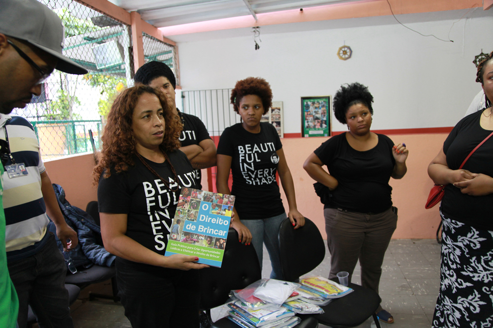Neia Bueno presents group with copies of the book offering a practical guide to create recreational opportunities and carry the right to play for kids in Brazil.