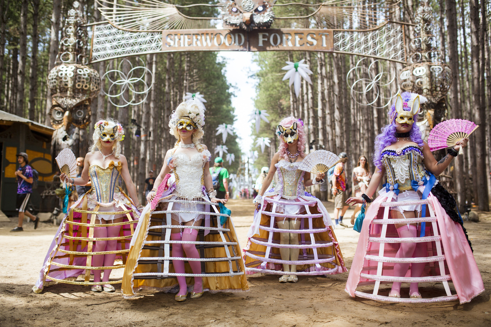 Hired performers dressed in cage dresses and masks greet festival goers as they enter the Sherwood Forest June 27 during the 5th Annual Electric Forest Festival in Rothbury, Mich.