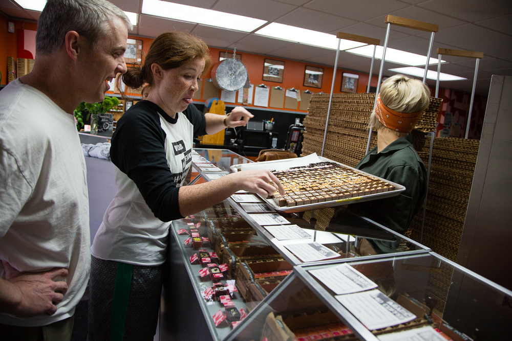 Berkley residents Steve Rose, left, watches as his daughter Hannah sneaks a bonbon from the new summer collection as soon while Clark is distracted from the batch Saturday, June 20 at Bon Bon Bon in Hamtramck, Mich.