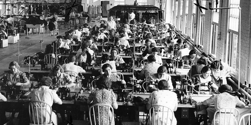 Women sewing at long tables next to tall windows  by  Kheel Center  is licensed under  CC BY 2.0 .