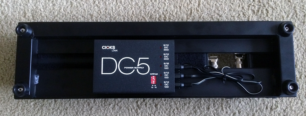The Cioks DC5 power supply mounted under a Pedaltrain Nano+ pedalboard.