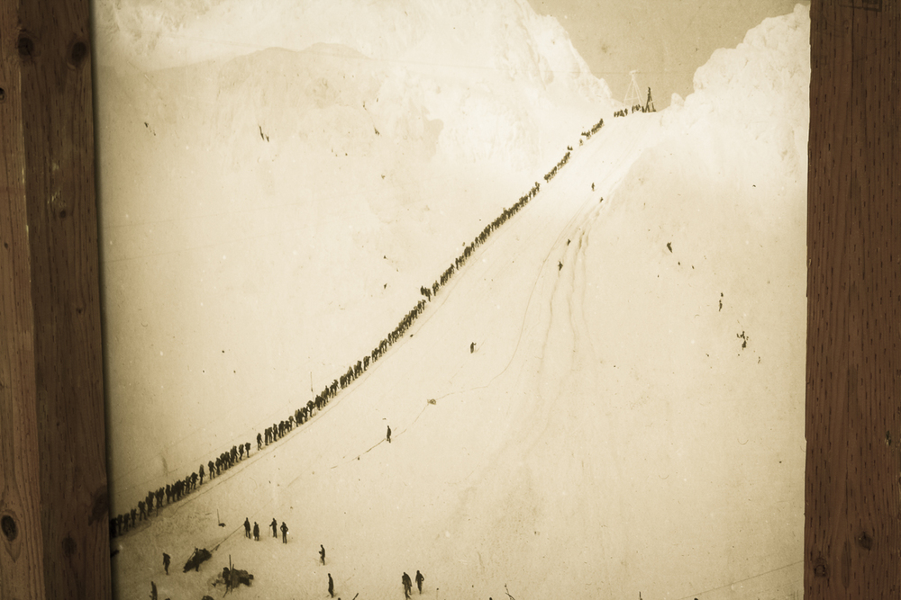 An old photo of men queuing through a pass on the Chilkoot Trail.