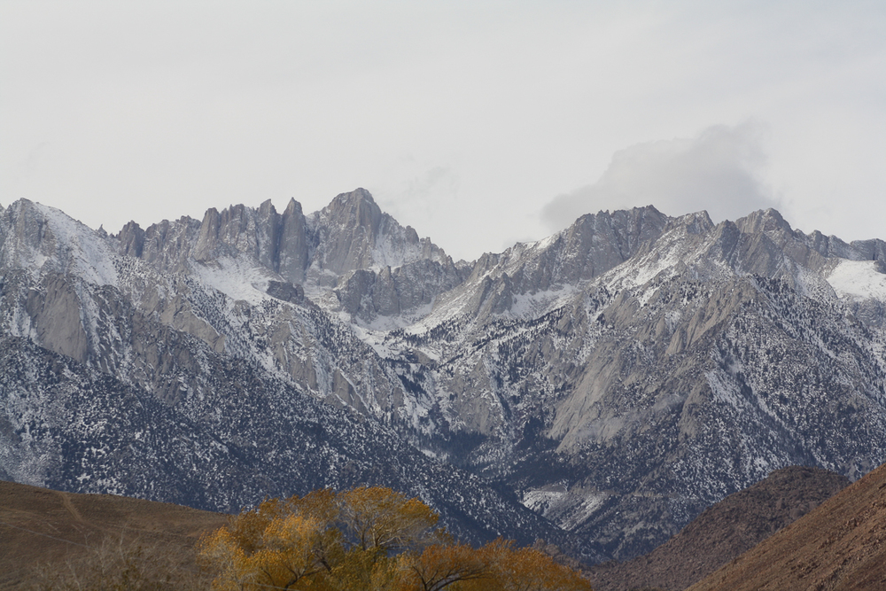 Mount Whitney from Lone Pine under a washed-out, cloudy sky.