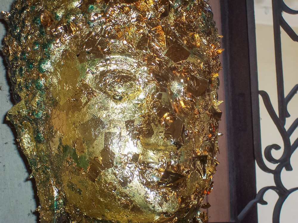 Placing gold leaf to a Buddha statue  is one part of making an offering during prayer.