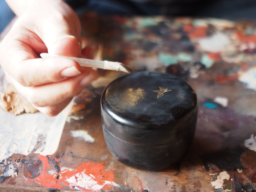 Applying the gold evenly on the surface can be very difficult and requires high skill. In this process, they will use a bamboo tool since the maki-e and the powder is delicate. ©TOKI