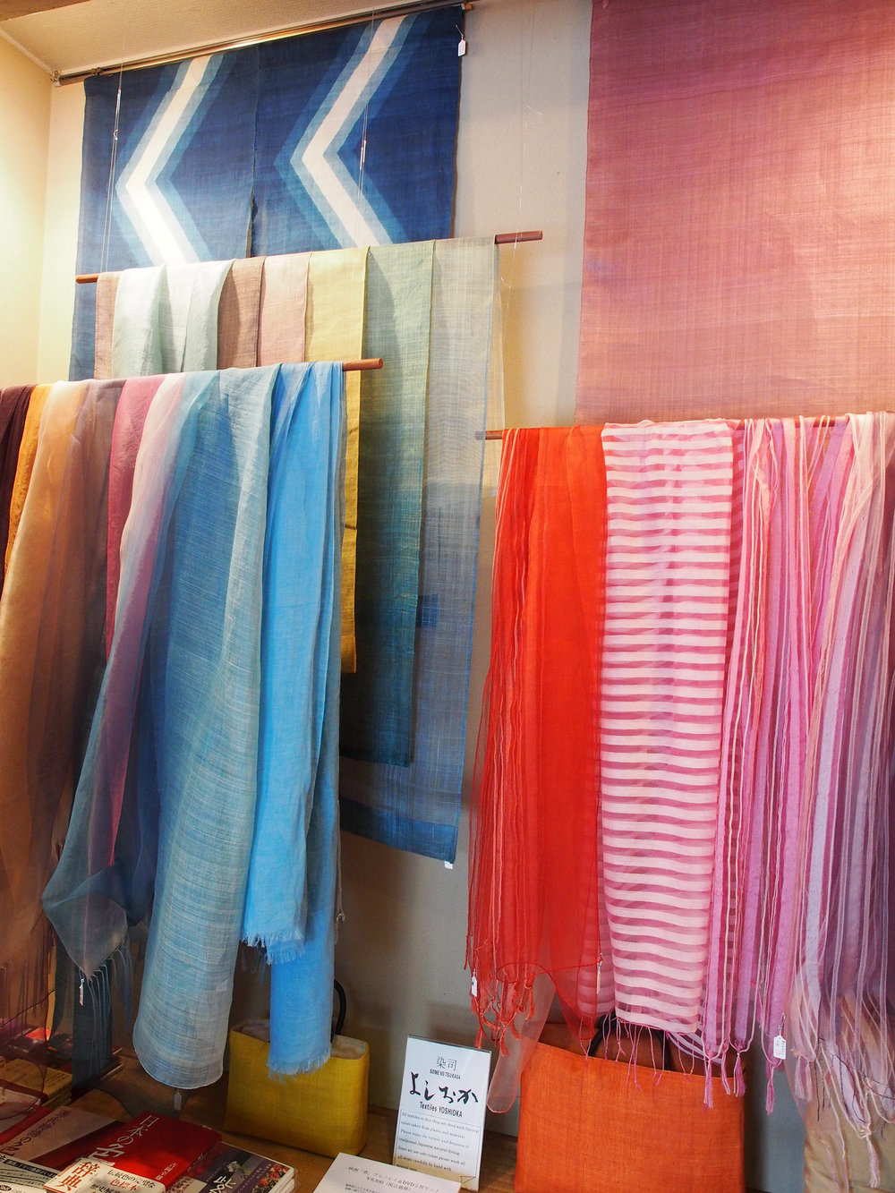 Some of the finished products that Yoshioka has created using his dyes. He makes a variety of unique, modern items (such as scarves and bags) as well as traditional textiles that are used in temples and shrines. ©TOKI