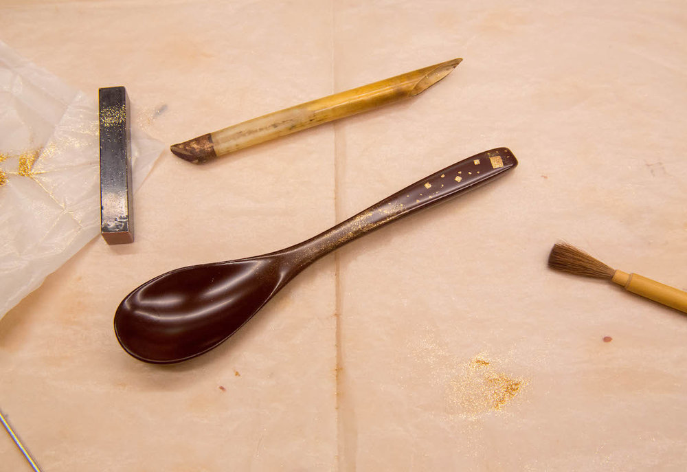 A lacquer spoon after applying gold leaf using traditional tools.