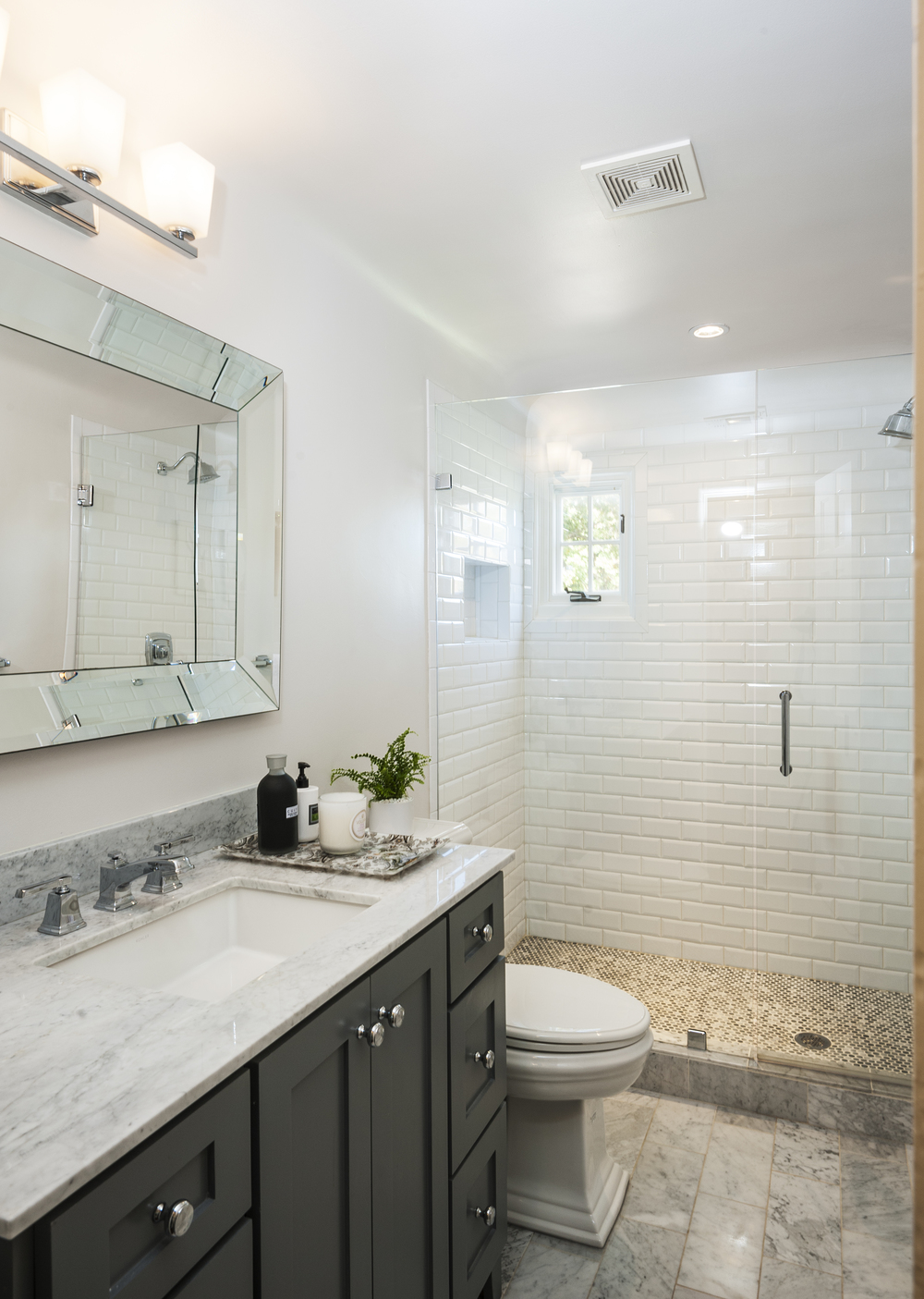 Alexis Pearl Design | Bathroom, white marble, white subway tile, glass shower door, grey vanity, modern and white, Pottery Barn Bevel wall mirror