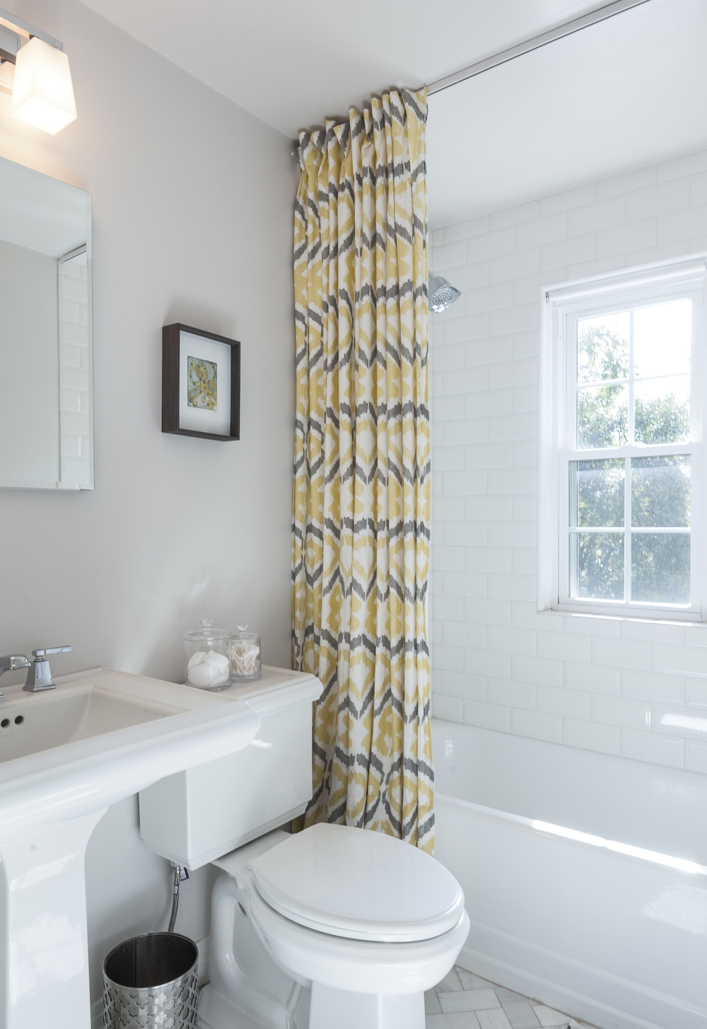 Alexis Pearl Design | Bathroom, ceiling mounted shower curtain, marble herringbone, white subway tile, Kohler pedestal sink