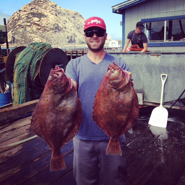 This is a photo of Chris Battle the dock manager at Morro Bay Fish Dock, where South Bay unloads holding up two of the biggest Petrale Sole either of us have ever seen.