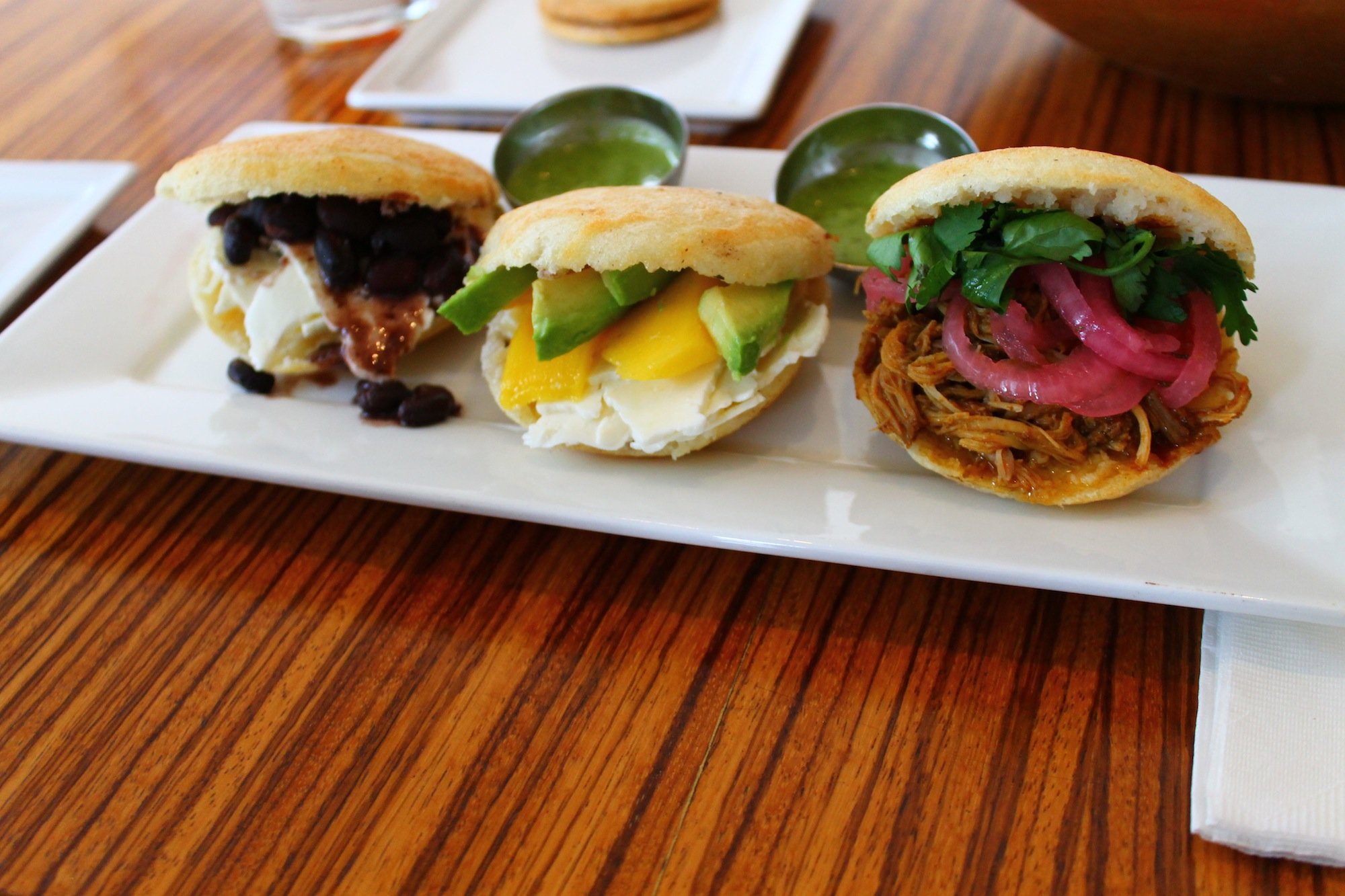 Arepas and guasacaca sauce.  From the left: black bean and fresh white cheese, mango avocado, pulled pork