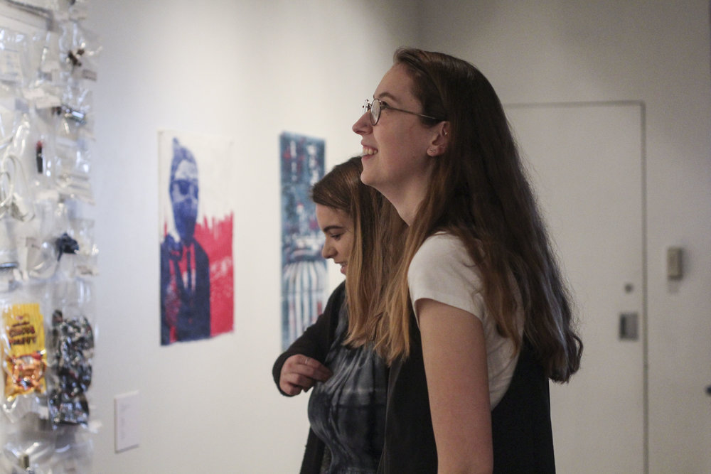 Student employees admire their work after installation of the Spring 2017 Senior Show.