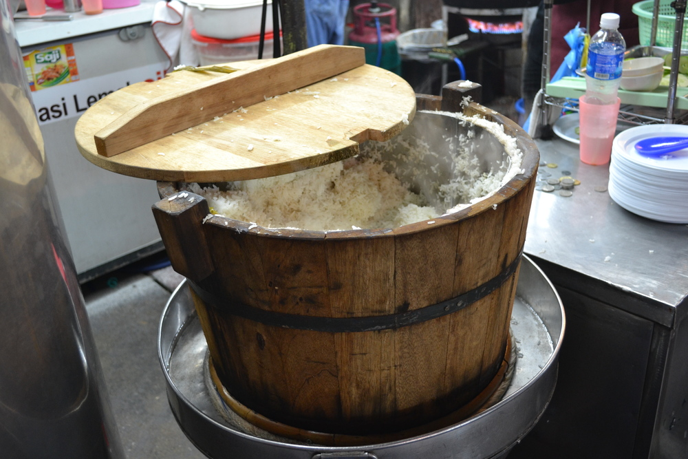 The coconut rice steamed in a wooden bucket.