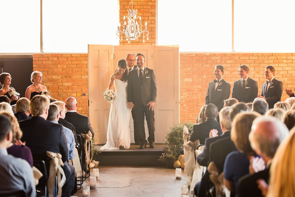 This indoor fall wedding was right about sunset. Light was coming in from both sides and tons of harsh light behind the couple but the space itself was pretty dark.