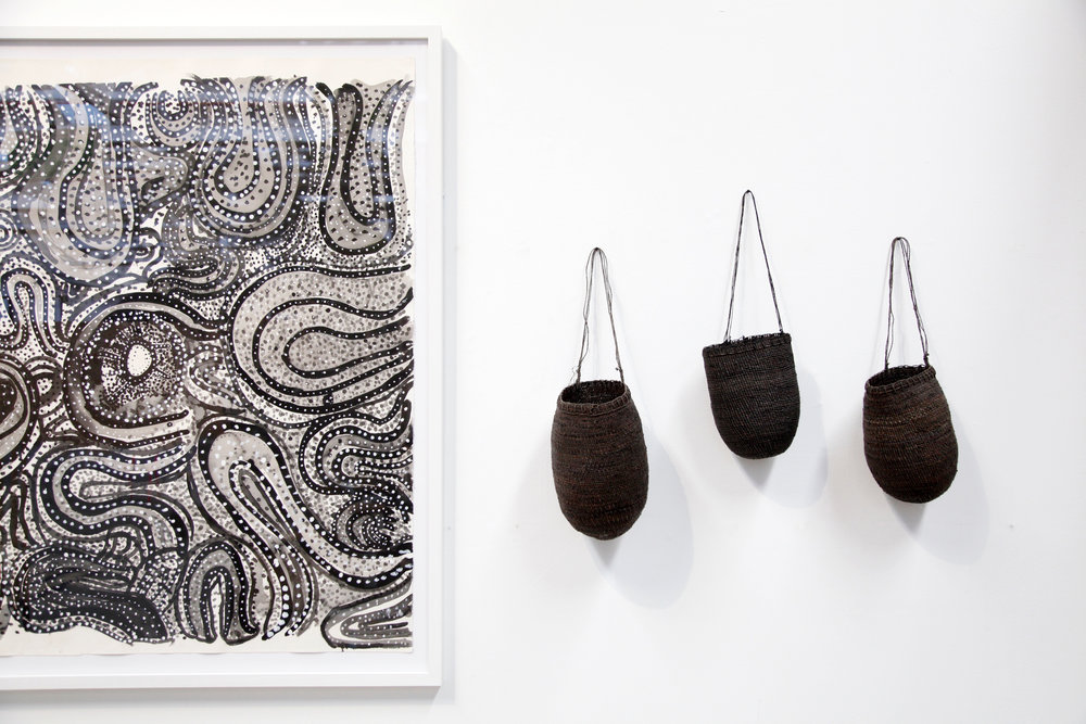 On left: Puna Yanima,Antara, ink on paper, 152 x 135cm, courtesy Mimili Maku Arts. (Bathi L-R): Margaret Rarru,Bathi mul, pandanus fibre, bush string and natural dyes, 34 x 21cm; Helen Ganalmirriwuy, Bathi mul, pandanus fibre, bush string and natural dyes, 29 x 17cm; Margaret Rarru,Bathi mul, pandanus fibre, bush string and natural dyes, 30 x 17cm. All works courtesy Milingimbi Art and Culture. Photo: Koskela.