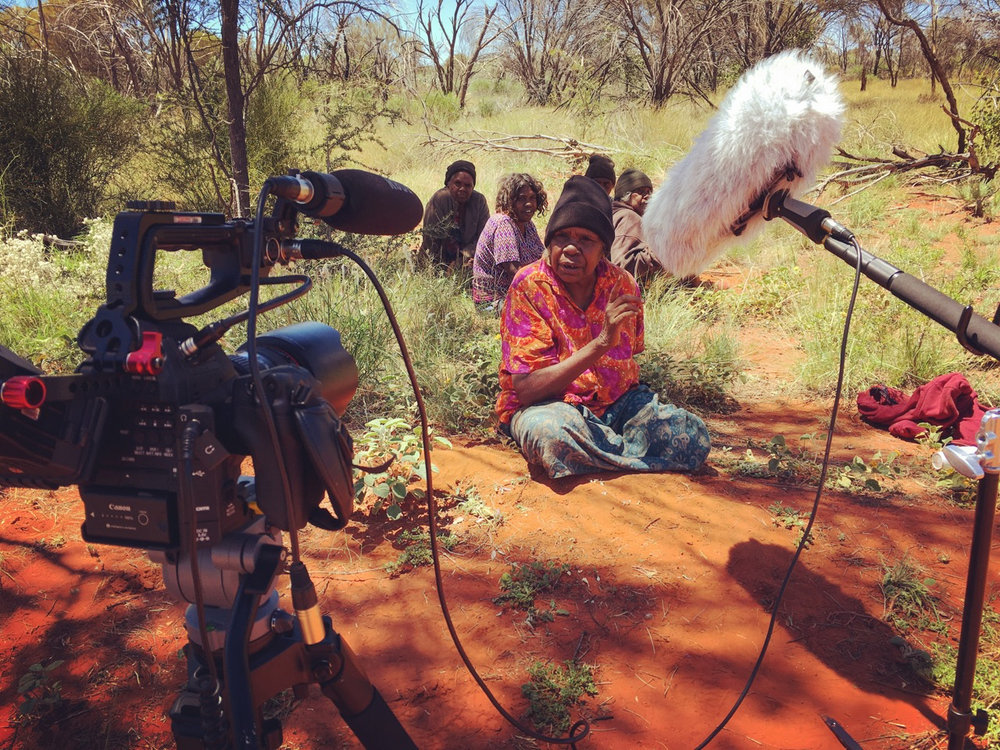Filming artist Daisy Kemarre Moss telling the story of her painting, outside of Ampilatwatja. Image courtesy  Lara Damiani
